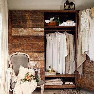 Modelo de armario de mujer, mediterráneo, de tamaño medio, con armarios con paneles lisos, puertas de armario de madera en tonos medios y suelo de cemento
