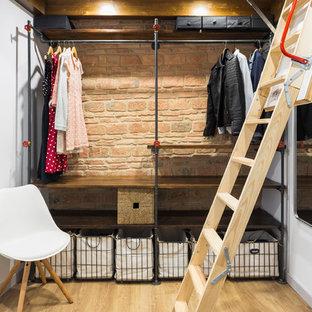Idee per una piccola cabina armadio unisex industriale con nessun'anta, ante in legno bruno e parquet chiaro