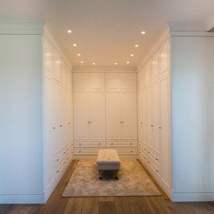 Modelo de vestidor unisex, clásico renovado, grande, con puertas de armario blancas y suelo de madera en tonos medios
