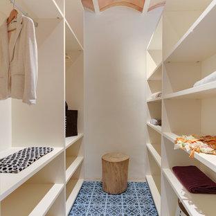 Diseño de armario vestidor unisex, mediterráneo, de tamaño medio, con armarios abiertos, puertas de armario blancas, suelo de baldosas de cerámica y suelo azul