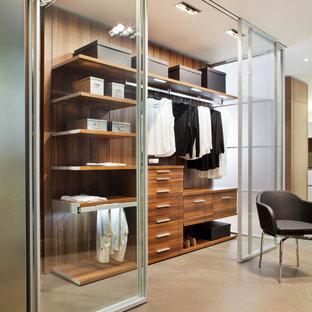 Idéer för mellanstora funkis walk-in-closets för kvinnor, med luckor med glaspanel, betonggolv och beiget golv
