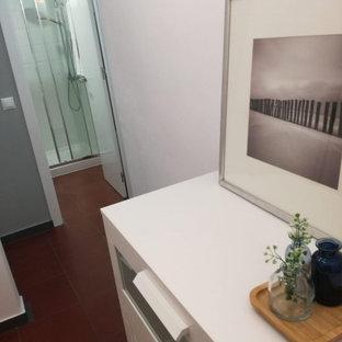 Immagine di un piccolo spazio per vestirsi unisex con ante con bugna sagomata, ante bianche e pavimento rosso