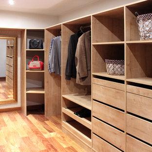 Diseño de vestidor de mujer, romántico, grande, con puertas de armario de madera clara y suelo de madera en tonos medios