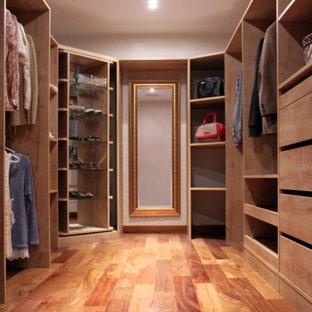 Imagen de vestidor de mujer, romántico, grande, con puertas de armario de madera clara y suelo de madera en tonos medios
