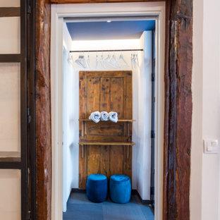 Modelo de vestidor de hombre, contemporáneo, pequeño, con armarios abiertos, puertas de armario de madera clara, suelo de linóleo y suelo azul