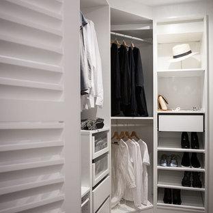 Diseño de armario vestidor unisex, actual, de tamaño medio, con armarios abiertos, puertas de armario blancas y suelo de madera en tonos medios
