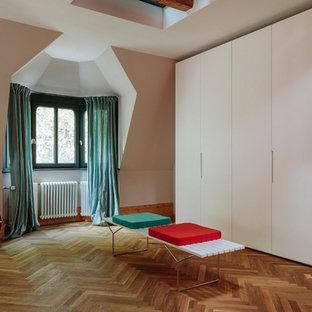 Foto de vestidor unisex, nórdico, grande, con armarios con paneles lisos, puertas de armario blancas, suelo de madera en tonos medios y suelo marrón