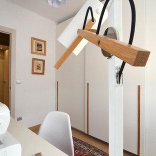 Foto de armario unisex, moderno, de tamaño medio, con armarios con paneles empotrados, puertas de armario blancas, suelo de madera en tonos medios y suelo marrón