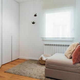 Foto de armario de mujer, escandinavo, de tamaño medio, con armarios con paneles lisos, puertas de armario blancas, suelo de madera en tonos medios y suelo marrón