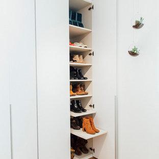 Foto de armario de mujer, nórdico, de tamaño medio, con armarios con paneles lisos, puertas de armario blancas, suelo de madera en tonos medios y suelo marrón