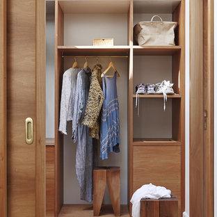 Foto de armario vestidor unisex, tradicional renovado, de tamaño medio, con armarios abiertos, puertas de armario de madera oscura y suelo de madera clara