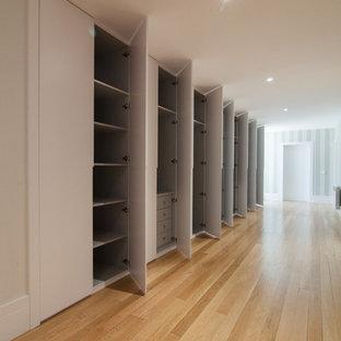 Modelo de armario unisex, tradicional renovado, extra grande, con armarios con paneles lisos, puertas de armario blancas y suelo de madera clara