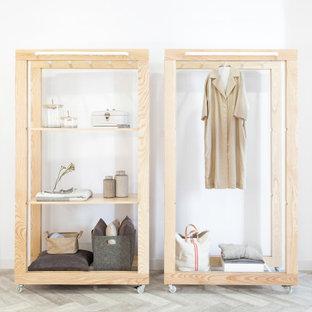 Immagine di un armadio o armadio a muro unisex industriale di medie dimensioni con nessun'anta, ante in legno chiaro, pavimento in gres porcellanato e pavimento grigio