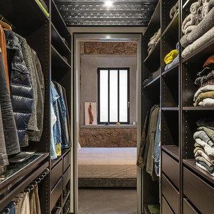 Modelo de armario vestidor unisex, industrial, de tamaño medio, con armarios abiertos, puertas de armario negras, suelo de cemento y suelo gris