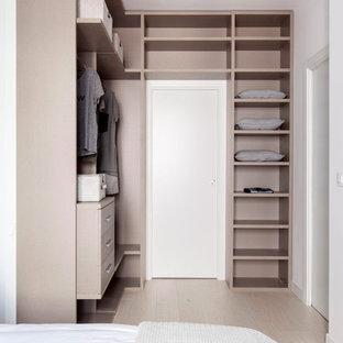 Ejemplo de armario vestidor unisex, contemporáneo, pequeño, con armarios abiertos, suelo de madera clara, suelo beige y puertas de armario beige