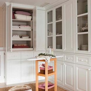 Foto di una cabina armadio unisex design di medie dimensioni con ante di vetro, parquet chiaro e pavimento beige