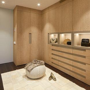 Imagen de armario vestidor de mujer, contemporáneo, con armarios con paneles lisos, puertas de armario de madera clara, suelo de madera oscura y suelo beige