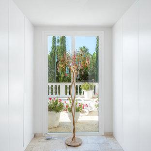 Ispirazione per una cabina armadio unisex mediterranea di medie dimensioni con ante lisce e ante bianche