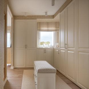 Modelo de vestidor unisex, clásico renovado, grande, con armarios con paneles con relieve, puertas de armario blancas, suelo laminado y suelo marrón