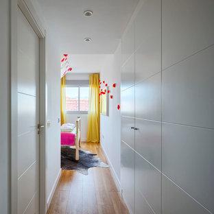Imagen de armario vestidor unisex, bohemio, grande, con armarios con paneles con relieve, puertas de armario blancas y suelo de madera en tonos medios