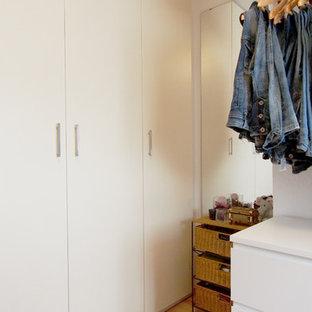 Diseño de vestidor de mujer, romántico, de tamaño medio, con armarios abiertos, puertas de armario blancas, suelo de madera clara y suelo marrón