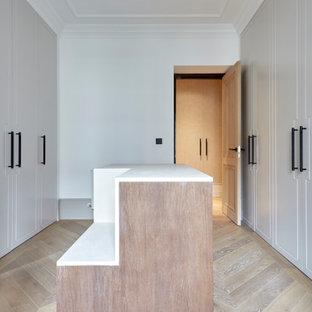 Modelo de armario vestidor unisex, tradicional renovado, grande, con armarios con rebordes decorativos, puertas de armario grises, suelo de madera clara y suelo multicolor