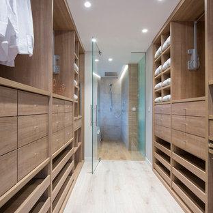 Diseño de armario vestidor unisex, actual, grande, con armarios abiertos, puertas de armario de madera oscura, suelo de madera clara y suelo beige