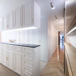 Ejemplo de vestidor unisex, contemporáneo, con armarios con paneles empotrados, puertas de armario blancas y suelo beige
