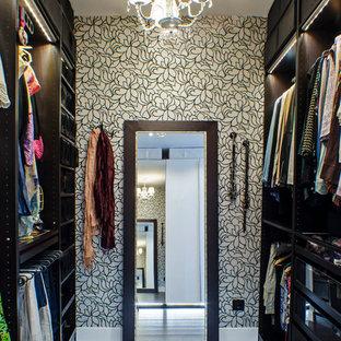 На фото: парадная гардеробная среднего размера в стиле современная классика с открытыми фасадами, черными фасадами, темным паркетным полом и коричневым полом для женщин с