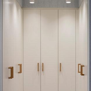 Idee per una cabina armadio unisex scandinava di medie dimensioni con ante lisce, ante bianche, pavimento in laminato e pavimento marrone