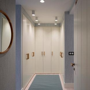 Foto di una grande cabina armadio unisex scandinava con ante lisce, ante bianche, pavimento in laminato e pavimento blu