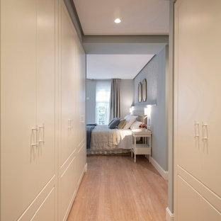 ビルバオの中サイズの男女兼用トランジショナルスタイルのおしゃれなウォークインクローゼット (インセット扉のキャビネット、白いキャビネット、ラミネートの床、茶色い床) の写真