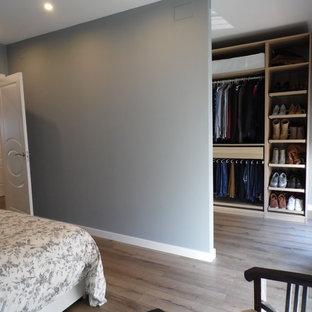 Esempio di una cabina armadio unisex nordica di medie dimensioni con pavimento in legno massello medio, nessun'anta e ante in legno chiaro