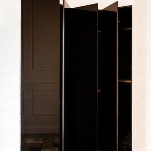 Idee per un armadio incassato unisex minimal di medie dimensioni con ante lisce, ante nere, pavimento in terracotta e pavimento multicolore