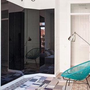 Modelo de armario y vestidor unisex, contemporáneo, de tamaño medio, con armarios con paneles lisos, puertas de armario negras, suelo de baldosas de terracota y suelo multicolor