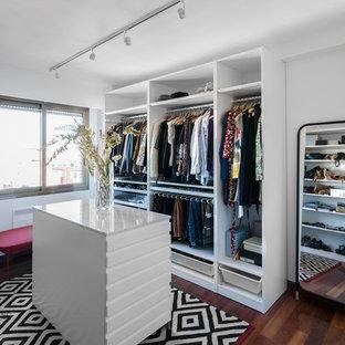 Diseño de armario vestidor unisex, contemporáneo, de tamaño medio, con armarios abiertos, puertas de armario blancas y suelo de madera oscura