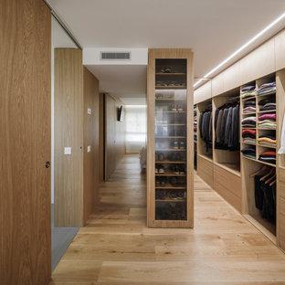 Diseño de armario vestidor de hombre, minimalista, con puertas de armario de madera oscura, suelo de madera en tonos medios, armarios con paneles lisos y suelo beige