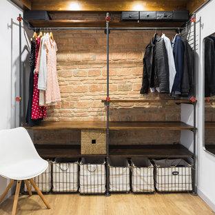Exempel på ett industriellt walk-in-closet för könsneutrala, med öppna hyllor, skåp i mörkt trä, ljust trägolv och beiget golv