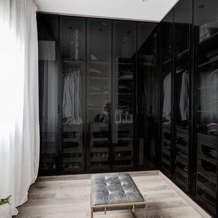 Esempio di uno spazio per vestirsi per uomo industriale di medie dimensioni con ante di vetro, ante nere, pavimento in laminato e pavimento marrone