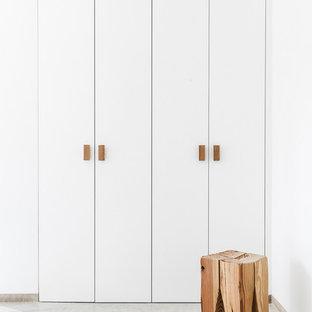 マヨルカ島の小さい男女兼用北欧スタイルのおしゃれな壁面クローゼット (フラットパネル扉のキャビネット、白いキャビネット) の写真