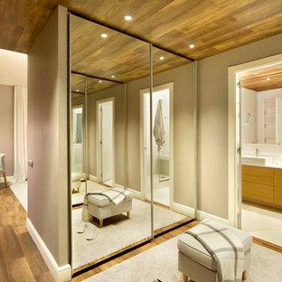 Immagine di una cabina armadio unisex minimal di medie dimensioni con pavimento in legno massello medio