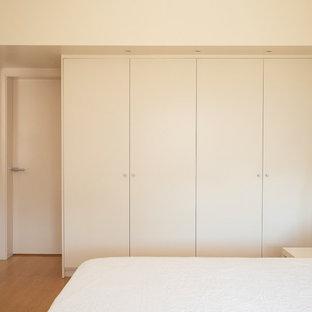 Ejemplo de armario y vestidor unisex, actual, de tamaño medio, con armarios con paneles lisos y puertas de armario blancas
