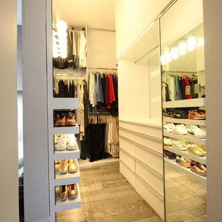 Diseño de armario vestidor de mujer, minimalista, grande, con armarios con paneles lisos, puertas de armario blancas, suelo de baldosas de porcelana y suelo gris