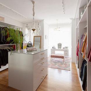 Ejemplo de vestidor de mujer, bohemio, grande, con armarios abiertos, suelo de madera en tonos medios y suelo beige