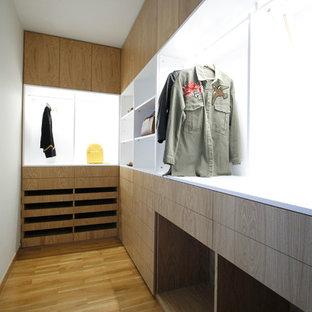 Ejemplo de armario vestidor contemporáneo, de tamaño medio, con armarios con paneles lisos, puertas de armario de madera clara y suelo de madera clara