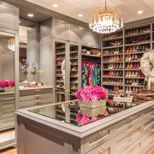 Diseño de vestidor de mujer, clásico, grande, con armarios abiertos, suelo de madera en tonos medios y puertas de armario grises