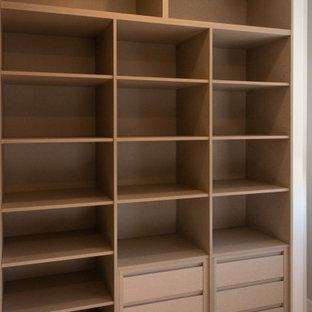 Imagen de armario vestidor unisex, moderno, con armarios abiertos, puertas de armario marrones, suelo de madera en tonos medios y suelo marrón