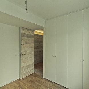Ejemplo de armario y vestidor nórdico, de tamaño medio, con suelo de madera clara