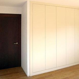 Diseño de armario vestidor unisex, rústico, pequeño, con armarios con paneles lisos, puertas de armario blancas y suelo de madera en tonos medios