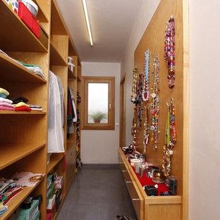 Inspiration för stora moderna walk-in-closets för könsneutrala, med öppna hyllor, skåp i mellenmörkt trä, klinkergolv i keramik och grått golv